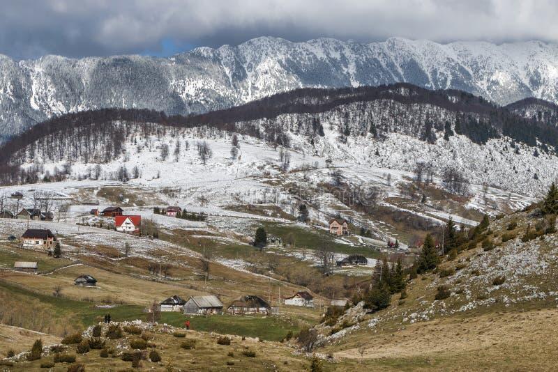 Zima wiejski krajobraz z tradycyjnymi gospodarstwo rolne domami blisko Piatra Craiului masywu w Sirnea wiosce, Brasov okręg admin zdjęcie stock