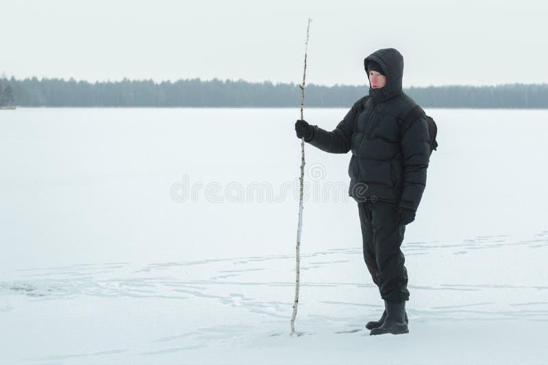 Zima wycieczkowicz bada śnieżną mroźną równinę z brzoza chodzącym kijem obraz royalty free