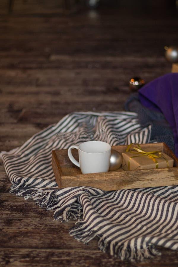 Zima wystrój: filiżanka kawy, prezent, taca, pasiasta szkocka krata, balowa i wygodna Wybrana ostrość obrazy stock