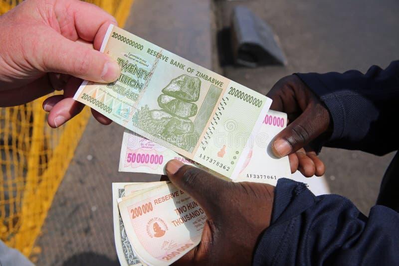 Zimbabwe Dollars. Two men changing Zimbabwe Dollar royalty free stock images