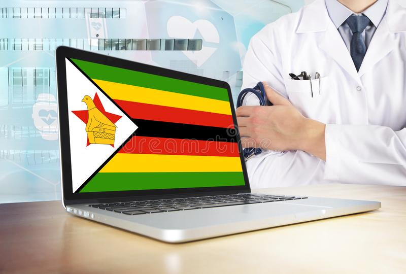 Zimbabwe vårdsystem i techtema Zimbabwisk flagga på datorskärmen Doktor som står med stetoskopet i sjukhus royaltyfri foto