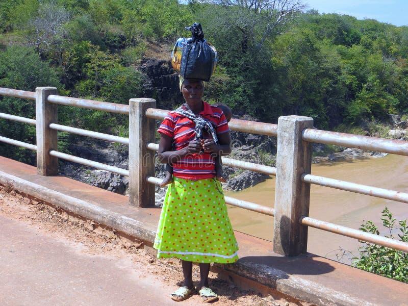 Zimbabwian-Frau auf der Brücke mit Sack auf ihrem Kopf lizenzfreie stockfotografie