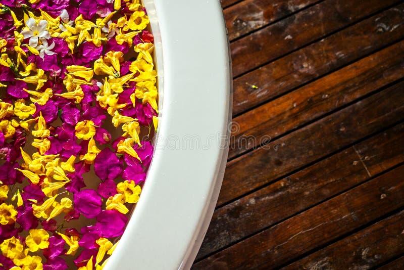 Zimmer mit Klimaanlage, Klimaanlage, Klimaanlage, Klimaanlage. Badewanne mit tropischen Blütenblättern Rundwhirlpool stockfotografie