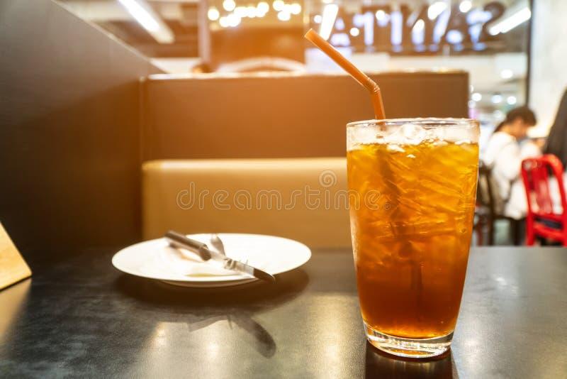 Zimna cytryny herbata na stole Z talerzami i łyżkami obraz stock