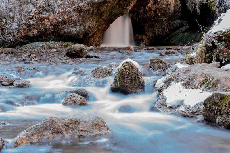 Zimna halna rzeka płynie między kamieniami z śniegiem i lodem, selekcyjna ostrość, siklawa w tle, długi ujawnienie, Karachay- obraz stock