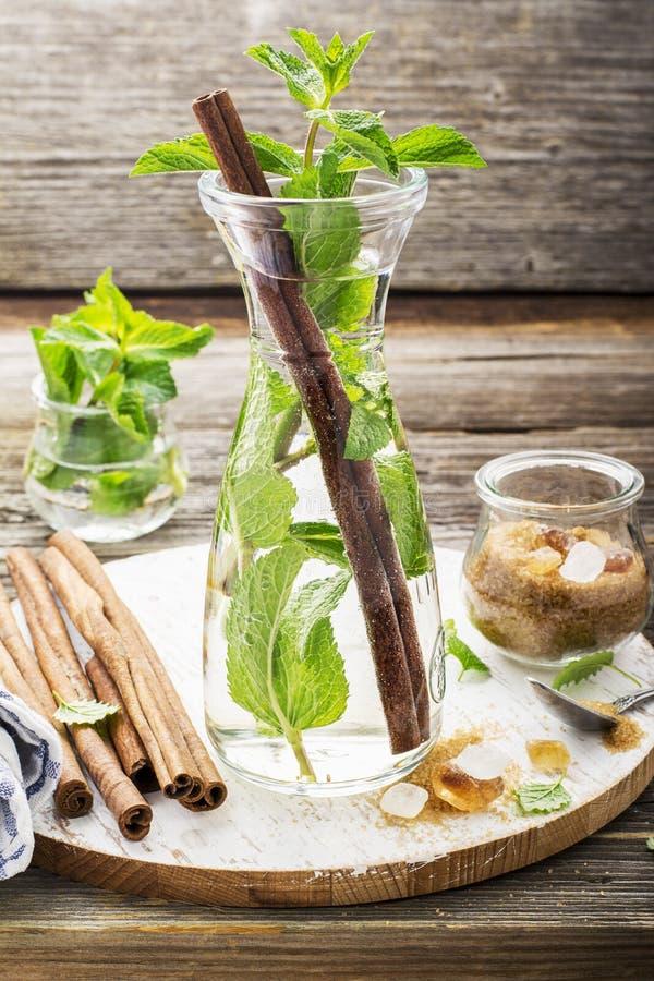Zimna odświeżająca Marokańska herbata z cynamonem i mennicą w wysokim dekantatorze na prostym drewnianym tle z brown cukierem fotografia royalty free