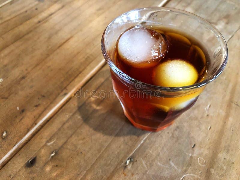 Zimna parzenie kawa, lód w szkle na drewnianym stole z naturalnym światłem i obrazy royalty free