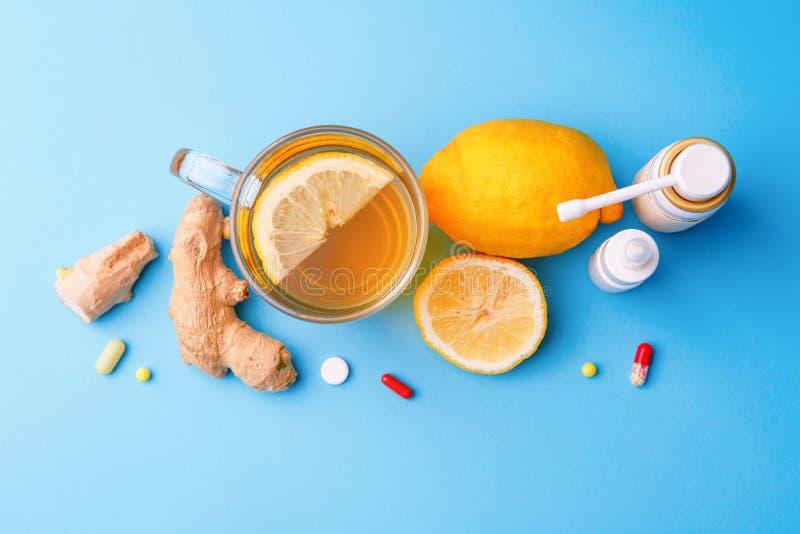 Zimne medycyny, herbata, cytryna i imbir na b??kitnym tle, obraz royalty free
