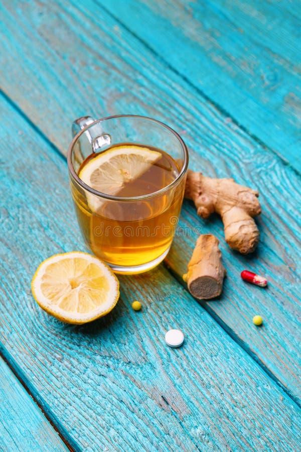 Zimne medycyny, herbata, cytryna i imbir na drewnianym b??kitnym tle, obraz royalty free