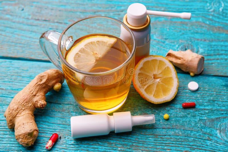 Zimne medycyny, herbata, cytryna i imbir na drewnianym b??kitnym tle, zdjęcie royalty free