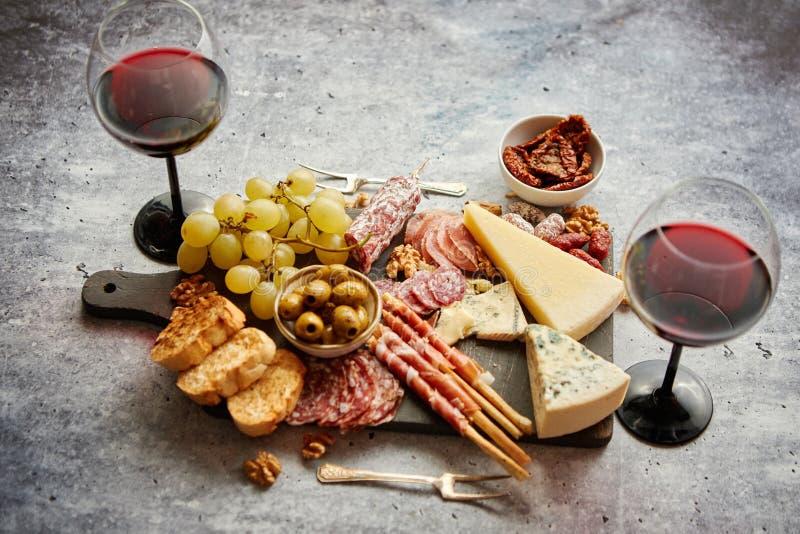 Zimne przekąski wsiadają z mięsami, winogrona, wino, różnorodni rodzaje ser fotografia stock