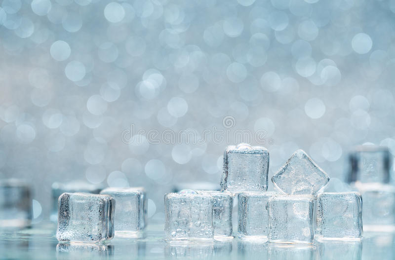Zimne roztapiające kostki lodu z wodnymi kroplami na blured tle zdjęcie royalty free