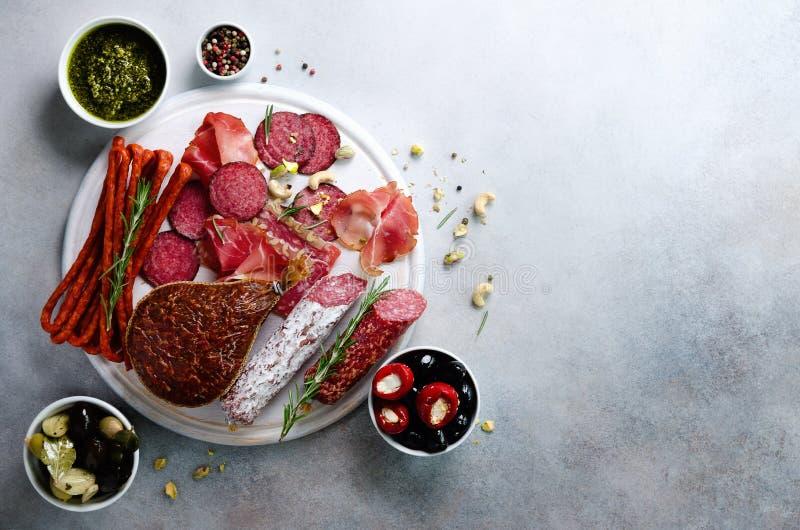 Zimno dymiący mięso talerz Tradycyjny włoski antipasto, tnąca deska z salami, prosciutto, baleron, wieprzowina kotleciki, oliwki  zdjęcia stock