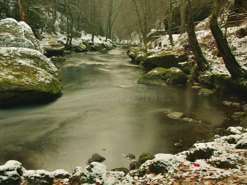 Zimno jasnego woda halna rzeka w zima czasie, sople na głazie obraz royalty free