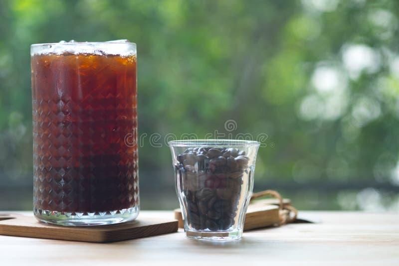 Zimno warzył lukrową kawę w wysokim szkle z kawowymi fasolami fotografia royalty free