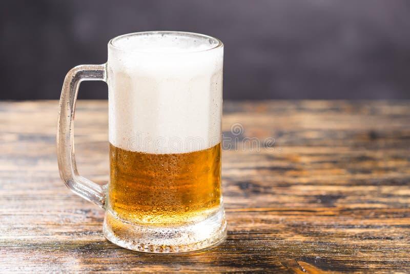 Zimny szkło lager piwo z pianą i rosa na ciemnym tle z kopii przestrzenią zdjęcia royalty free