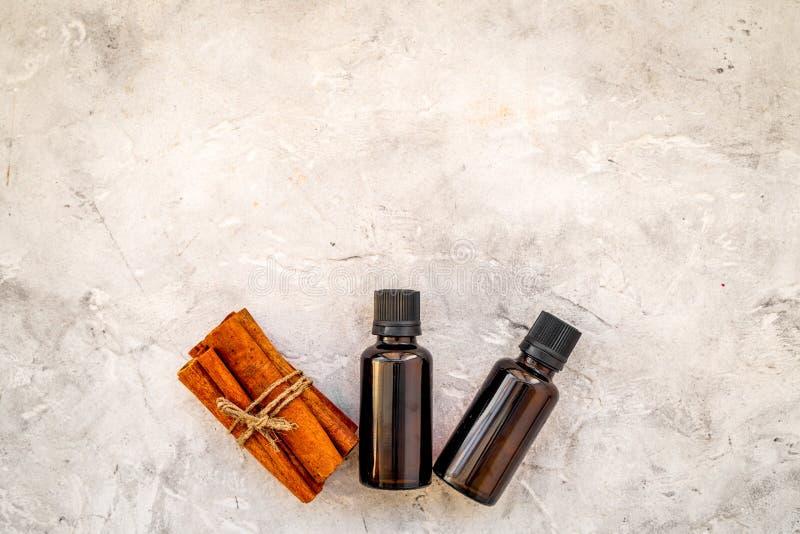 Zimtöl für das Kochen, aromatheraphy, Hautpflege Flaschen nahe Zimtstangen auf grauem Hintergrundraum für Text lizenzfreies stockfoto