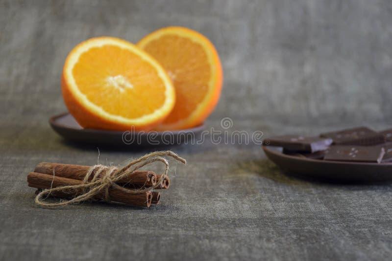 Zimtstangen, geschnittene Orange und Stücke dunkle Schokolade lizenzfreie stockbilder