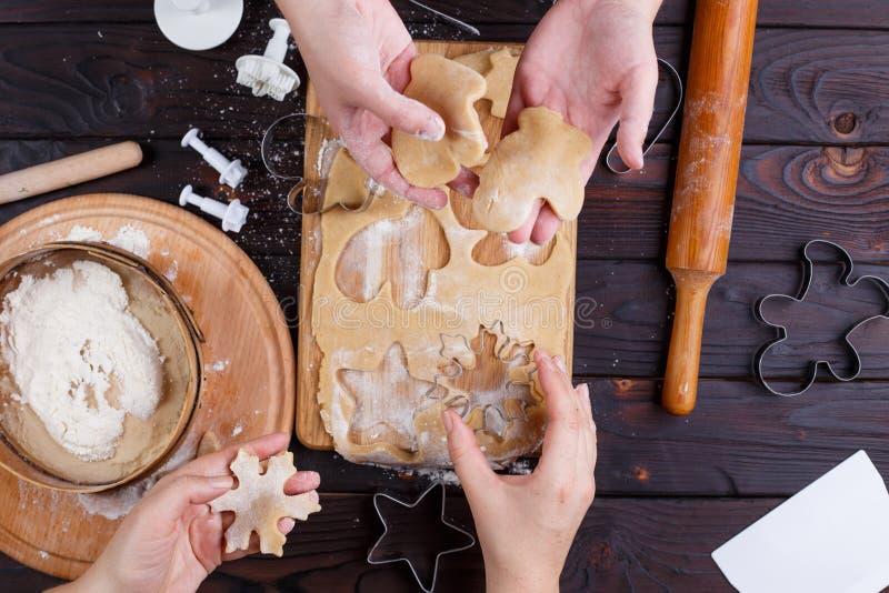 Zimtsterne und Sternanis auf hölzernem Hintergrund mit Zuckerpulver Freunde, die den Lebkuchen, Plätzchen von schneiden machen stockfotografie