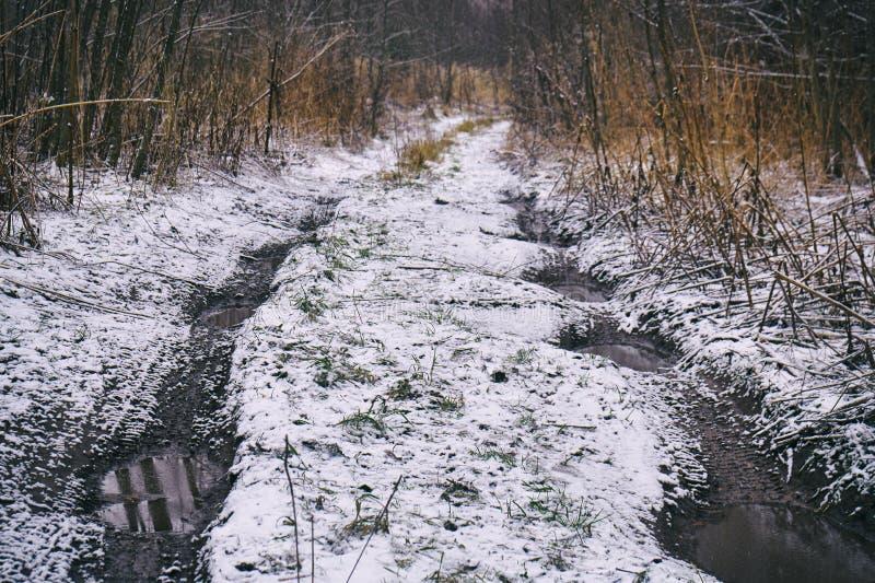 Zimy śnieżna droga gruntowa z dużymi kałużami woda zdjęcie stock