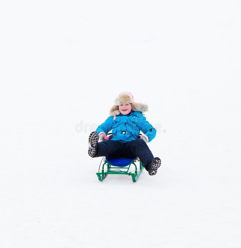 Zimy aktywna zabawa - szczęśliwa dziewczyna jedzie śnieżnego wzgórze na saniu obrazy royalty free