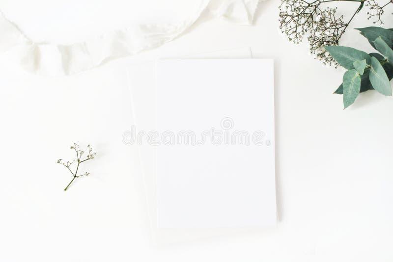Zimy desktop materiały ślubny mockup Pusty kartka z pozdrowieniami, dziecka ` s oddechu łyszczec kwitnie, eukaliptus gałąź i fotografia stock
