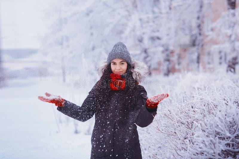 Zimy dziewczyna w czerwonych rękawiczkach i szalika podmuchowym śniegu Piękno Radosna Nastoletnia Wzorcowa dziewczyna ma zabawę w zdjęcie stock