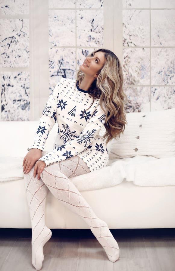 Zimy kobiety salowy portret Młoda piękna blond dziewczyna w trykotowym odziewa śnieżnym okno w domu Mody stylowy płótno obraz royalty free