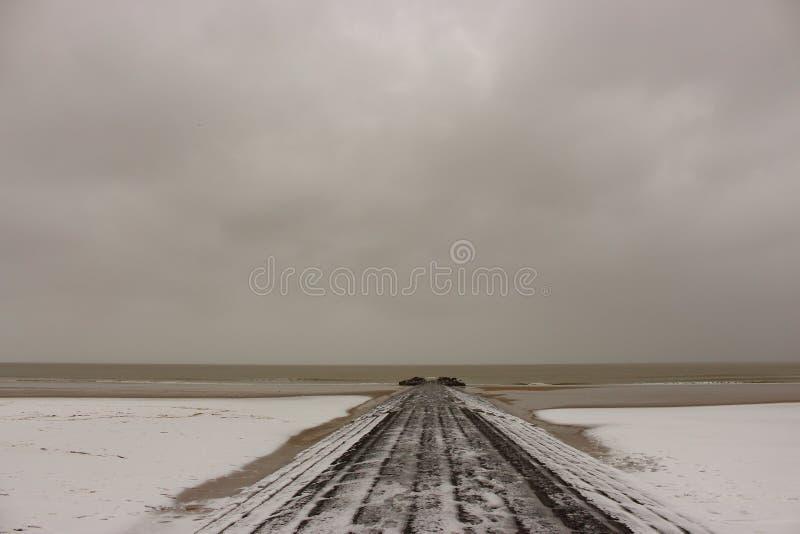 Zimy molo w śniegu na chmurnym dniu przy Północnym morzem i plaża, Belgia, Blankenberge seashore lodowa denna zima Podróży i samo zdjęcie royalty free