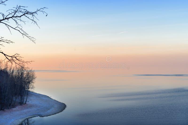 Zimy morze przy zmierzchem, jasny wieczór Pomarańcze i niebieskie niebo, brzeg zakrywający śnieg, nadzy drzewa fotografia stock