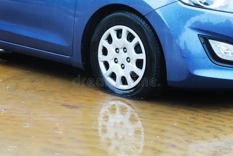 Zimy pogoda w Izrael: deszcz, kałuże, powodzie i wylew, Samochodowy toczy wewnątrz kałużę deszczówka, raindrops i woda okręgi, zdjęcia stock