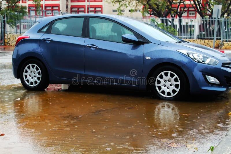 Zimy pogoda w Izrael: deszcz, kałuże, powodzie i wylew, Samochodowy toczy wewnątrz kałużę deszczówka, raindrops i woda okręgi, obraz stock