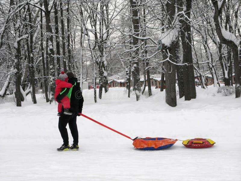 Zimy rozrywka, tata i dziecko, nadmuchiwani saneczki, ruruje zdjęcie stock
