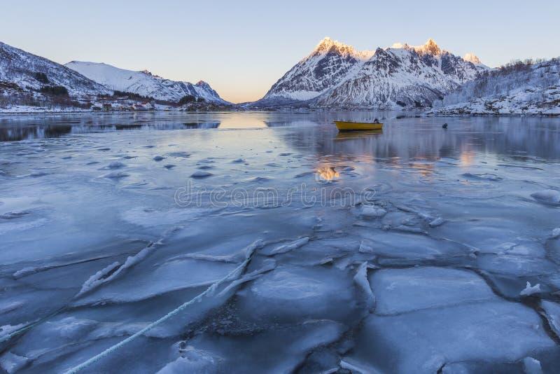 Zimy scena łódź w stronniczo marznącym fjord i śnieżnym mountai zdjęcia stock