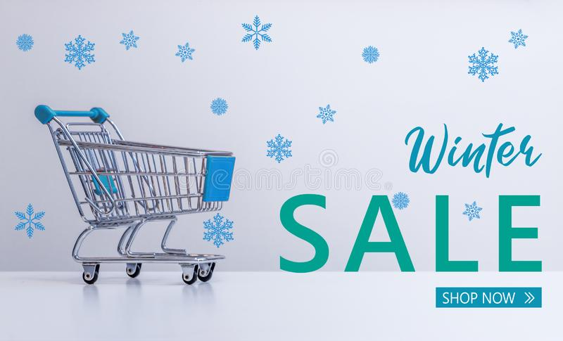 """Zimy sprzedaż: Wózka na zakupy i """"Winter sprzedaży †""""Robi zakupy now† literowanie royalty ilustracja"""