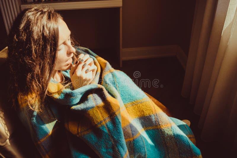 Zimy zimna pojęcie Młoda marznięcie kobieta w wygodnym krześle oddycha ciepłego powietrze na zamarzniętych rękach zawijać w ciepł obrazy stock