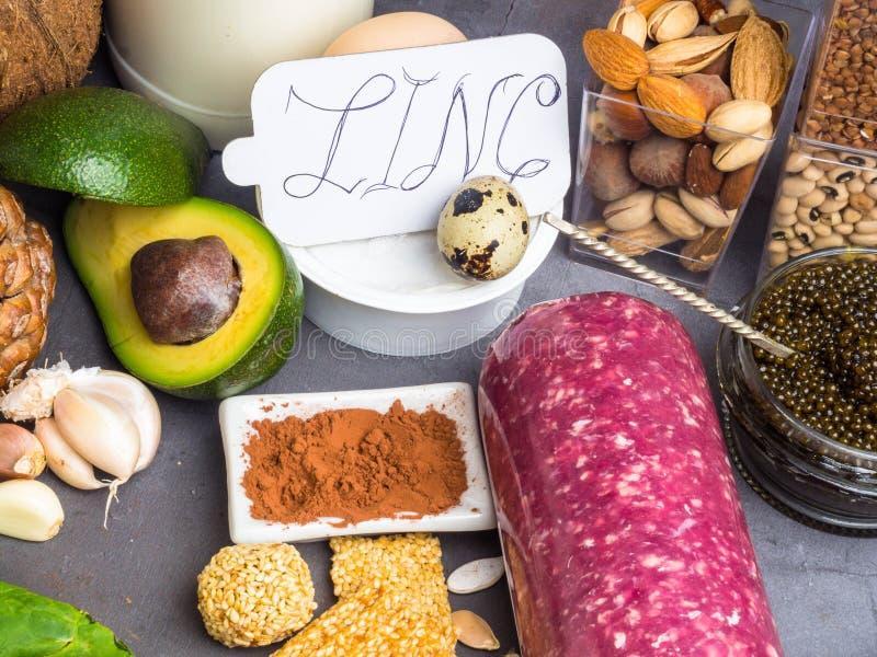Zinco, ingredientes ou produtos da inscrição contendo o zinco e a fibra dietética na placa cinzenta, fontes naturais de minerais imagens de stock royalty free