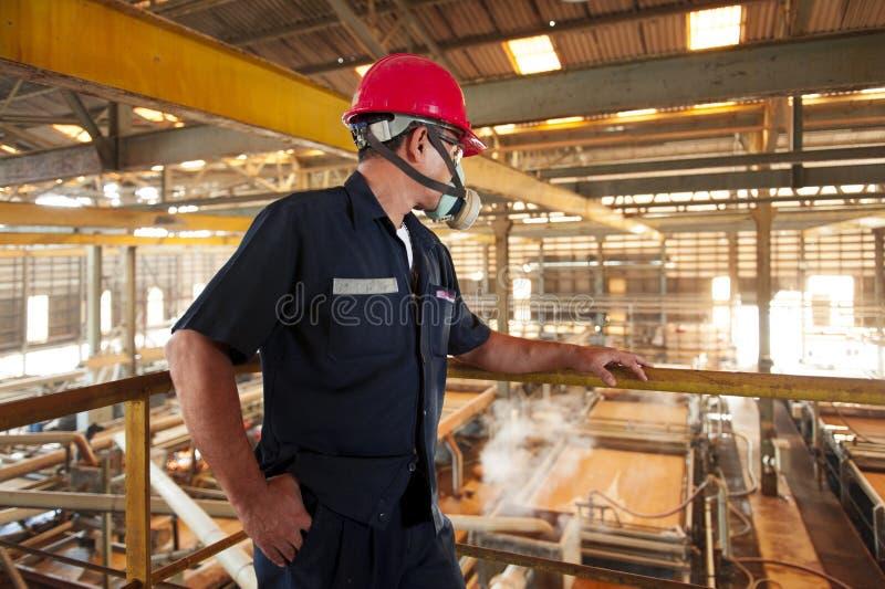 Zinkmin Tillbaka sikt av den säkra teknikern som ser fabriken som bryter och tänker arkivbild