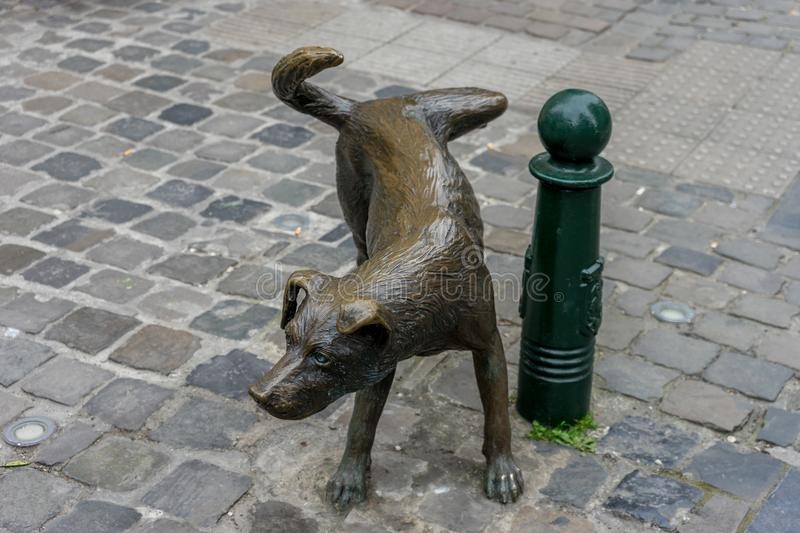 Zinneke Pis, Het Zinneke,Brown sculpture of a dog on a p. Zinneke pis, Het Zinneke, Brown sculpture of a dog on a pole on the streets of Brussels, Belgium stock photo
