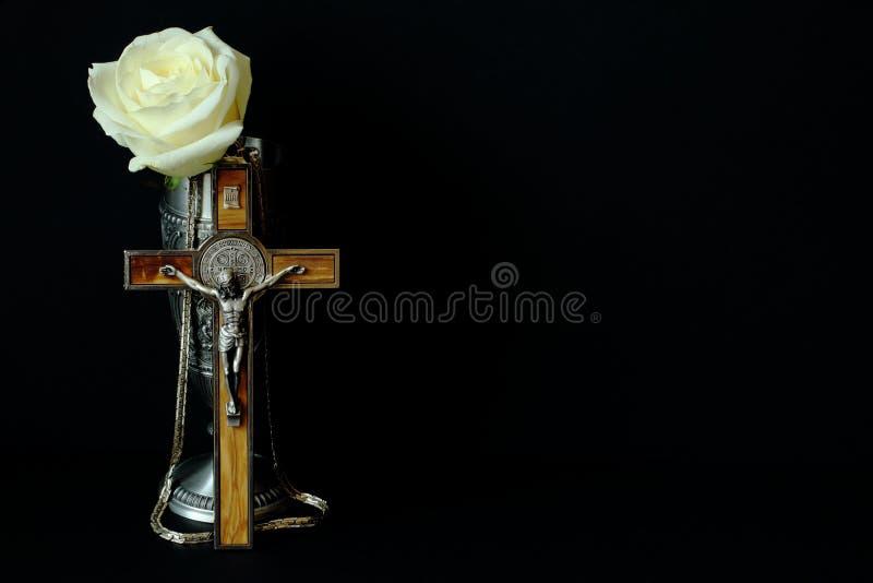 Zinnschale für Wein, Kruzifix mit hölzernen Einlegearbeitandenken aus Deutschland und weiße Rose auf schwarzem Hintergrund Symbol lizenzfreie stockbilder