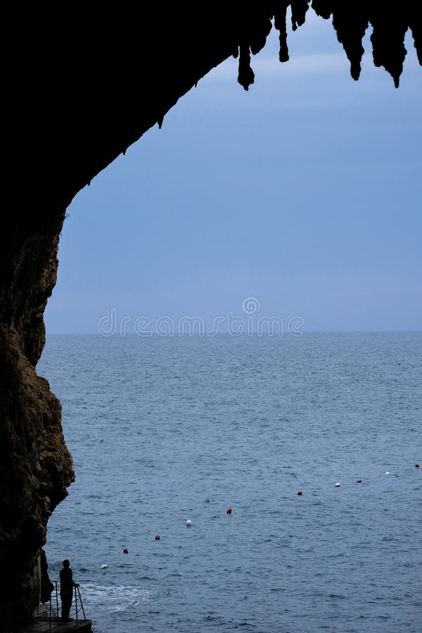Zinzulusa Caves, near Castro on the Salento Peninsula in Puglia, Italy. Person stands on gang plank at entrance to the caves. royalty free stock photos