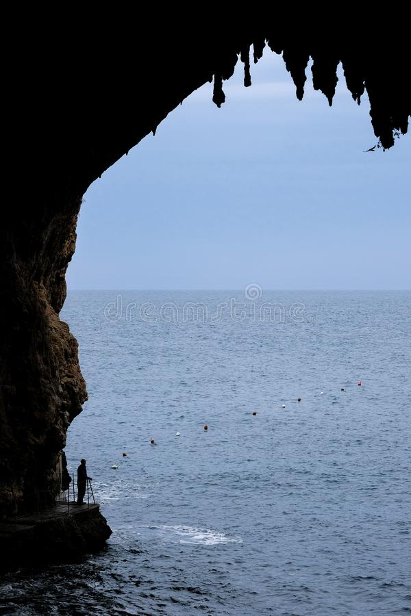 Zinzulusa Caves, near Castro on the Salento Peninsula in Puglia, Italy. Person stands on gang plank at entrance to the caves. Caves of Zinzulusa, near Castro on stock photography