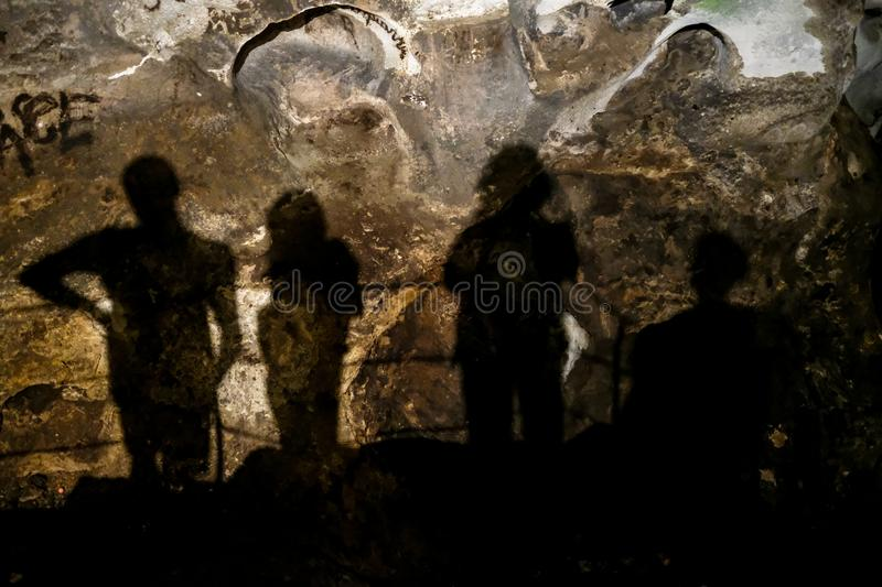 Zinzulusa Caves, near Castro on the Salento Peninsula in Puglia, Italy. Shadows of four people can be seen against the stone walls royalty free stock images