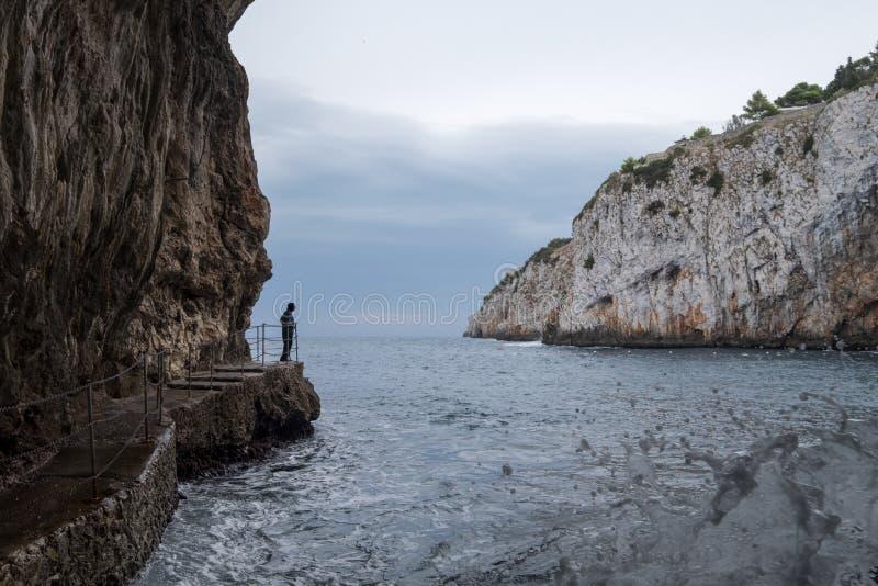Zinzulusa Zawala się, blisko Castro na Salento półwysepie w Puglia, Włochy Osoba stojaki na gang desce przy wejściem jamy obrazy royalty free