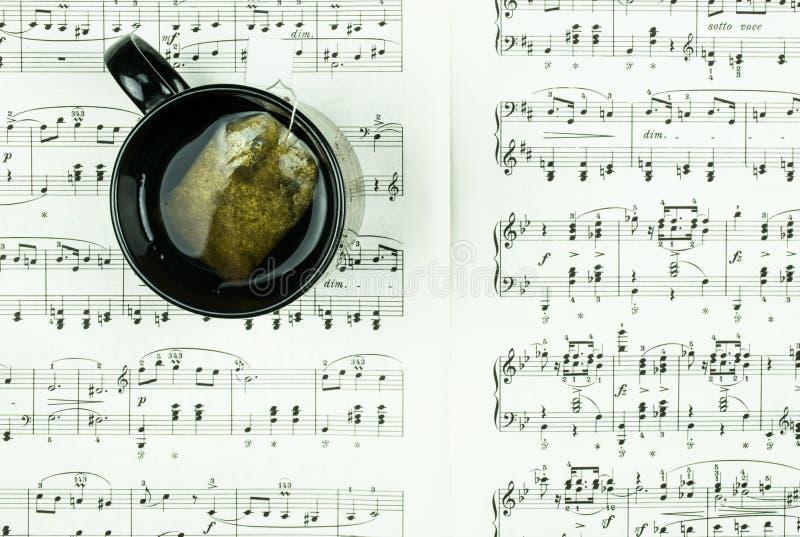 Ziołowa herbata w czarnej filiżance na prześcieradle z klasycznymi muzyk notatkami jako tło zdjęcie stock