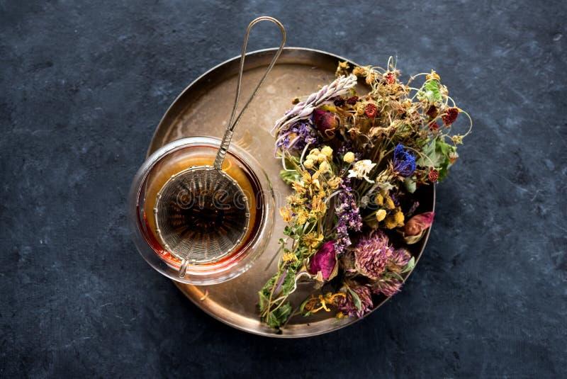 Ziołowa herbata w filiżance, durszlaku i suszących medycznych ziele, zdjęcie royalty free