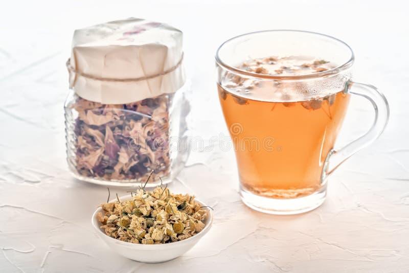 Ziołowa herbata z farmaceutycznym chamomile i słojem susi różani płatki na białym stole zdjęcie stock