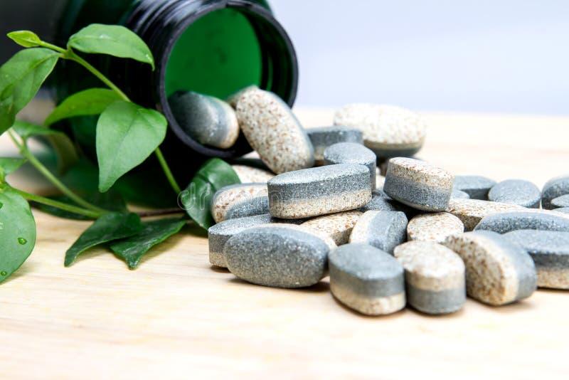 Ziołowe nadprogram witaminy pigułki lub pastylki na drewnianym talerzu obrazy stock