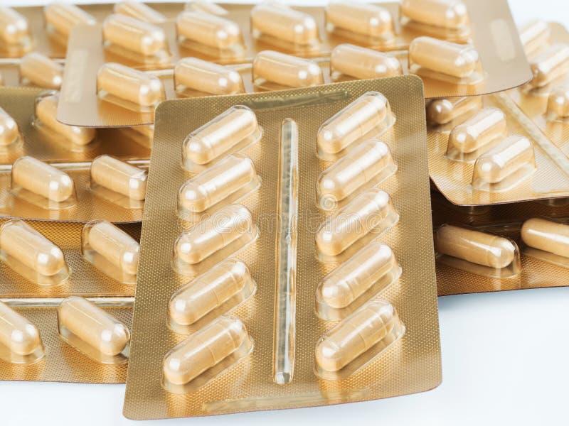 Ziołowej medycyny proszek zawierający w kapsułach na bielu zdjęcia stock