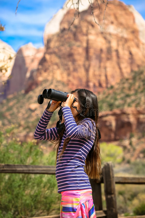 Zion National Park. Gril using binocular to look at the peek of of the mountain at Zion National Park royalty free stock photos